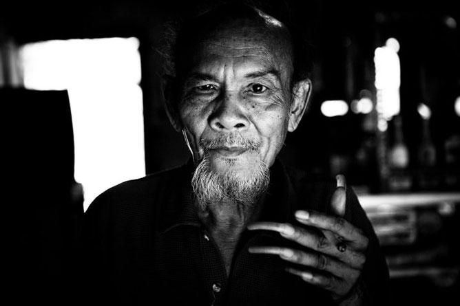 Hosszú körmű ázsiai férfi, fekete fehér kép.
