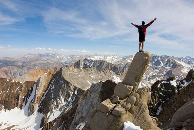 Hegycsúcs tetején széttárt karokkal álló férfi élvezi a tér végtelen szabadságát