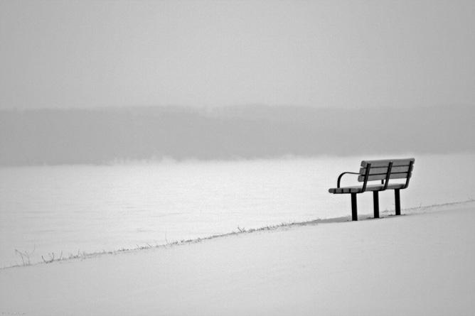 Havas táj egy magányos paddal.