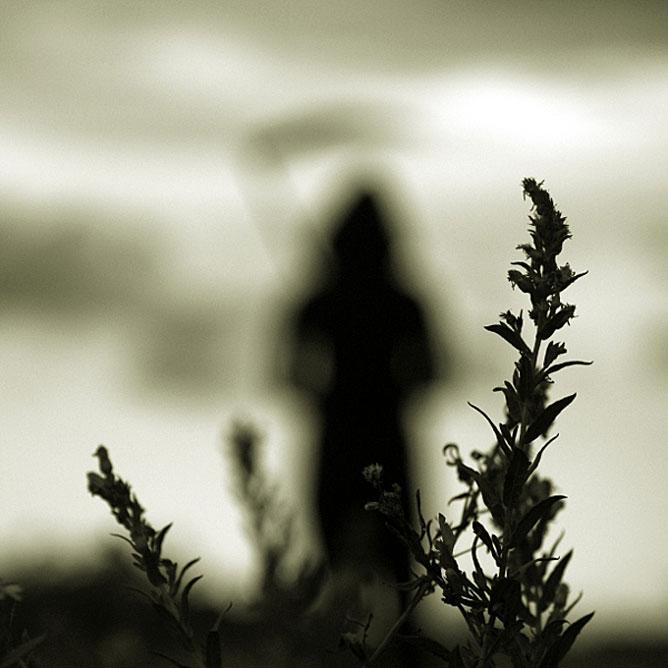 Sötét hangulatú kép a kaszás képében megjelenő halállal a háttérben