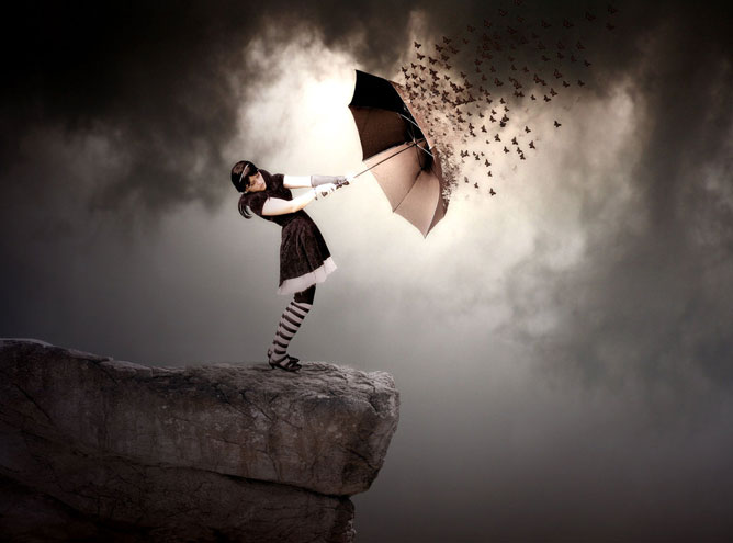 Szakadék szélén álló lány esernyővel a kezében, ami pillangókká foszlik szerte széjjel