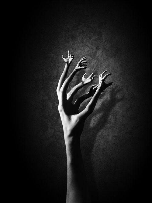 Fekete-fehér kép, karok nőnek ki a kéz ujjaiból.