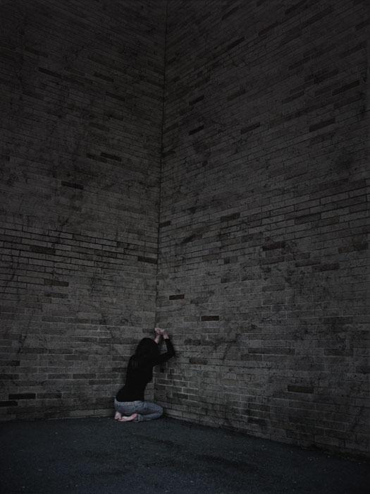 Egy lány a sötétben öklével üti az őt körbezáró tégla falakat.