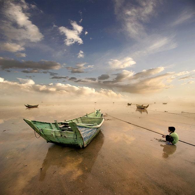 Rozzant csónakok a nedves homokban; guggoló gyermek; gyönyörű tengerparti tájkép.