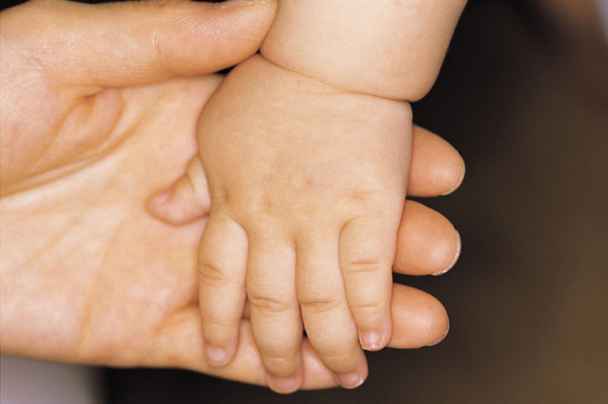 Egy gyermek keze egy felnőtt kezében.