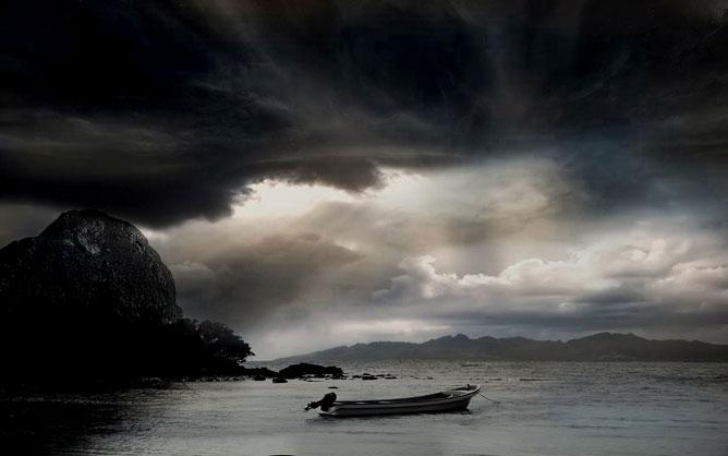 Vihar előtti tenger egy árválkodó csónakkal.