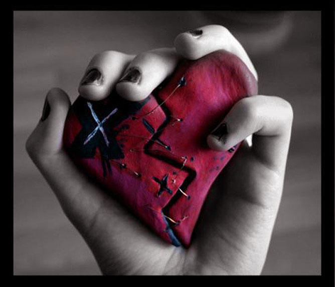 Összefoltozott piros szív egy kézben.