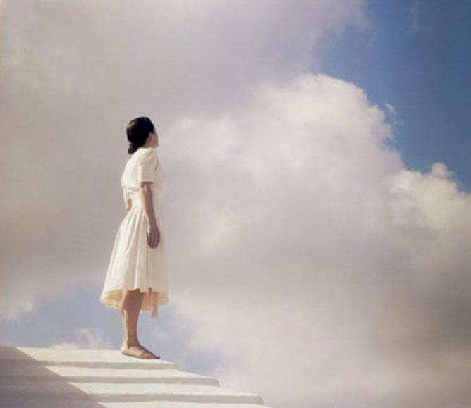 Fehér ruhás nő áll a felhők alatt.