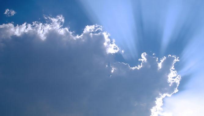 Felhő mögül kiáradó napfény.