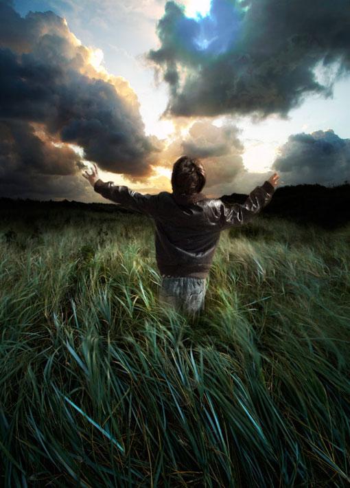Széttárt kezekkel lévő férfi a fűben kérdőre vonja az eget.
