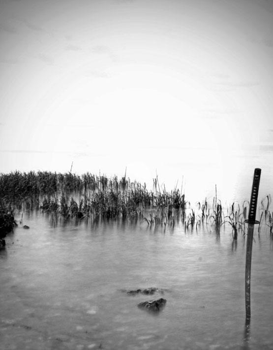 Szamurájkard a vízbe szúrva a parton.