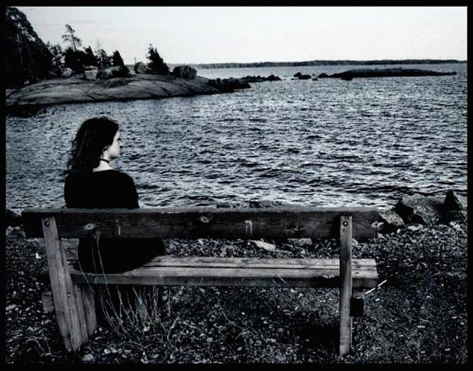 A vízparton egy padon magányosan ülő lány.