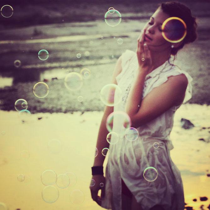 A pillanat átélése és a létezés élvezete; lány szappanbuborékokkal a tengerparton.