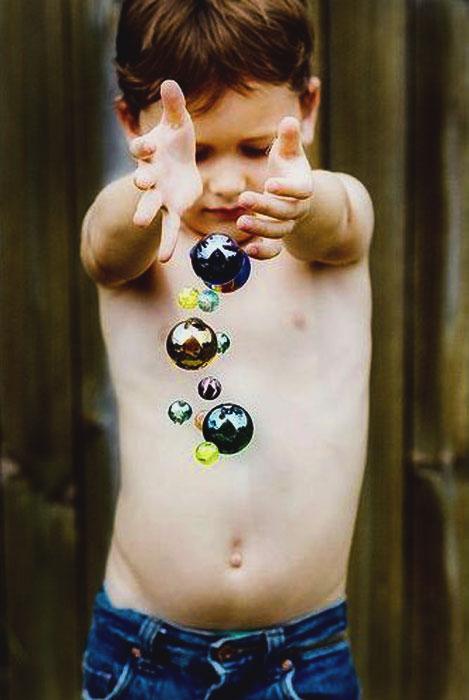 Üveggolyóval játszó kisfiú.