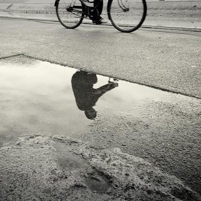 Bicikliző ember tükörképe egy tócsában.