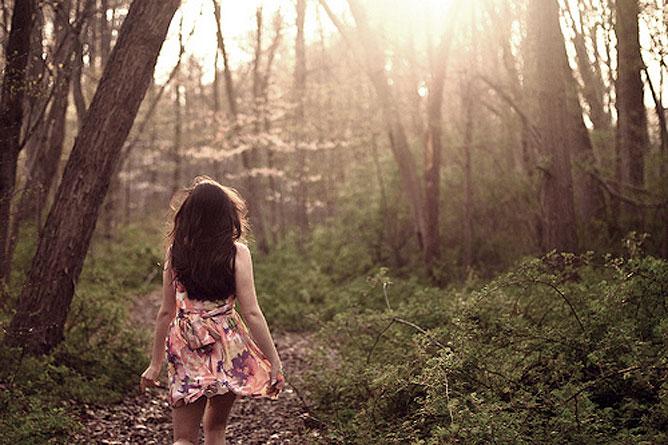 Sétáló lány az erdőben.