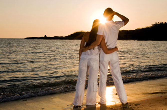 Szerelmespár a tengerparti naplementében.