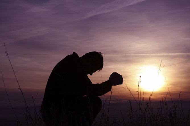 imádkozó férfi a naplementében.
