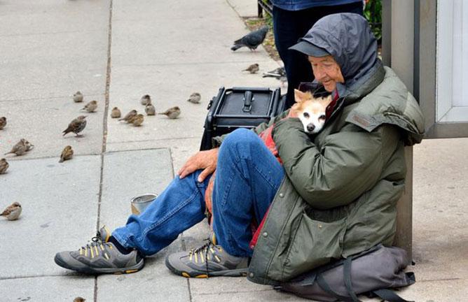 hajléktalan ember a kutyájával.